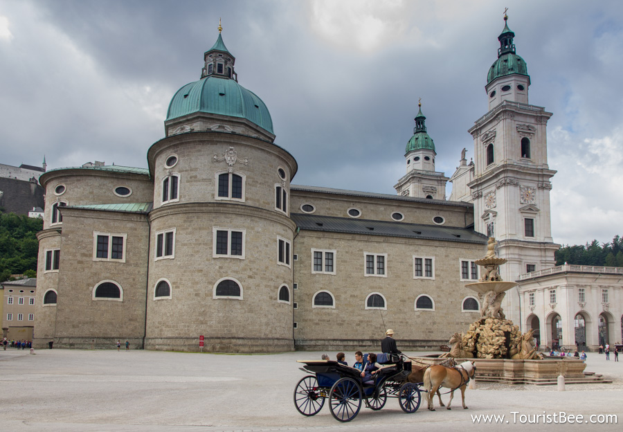 Salzburg, Austria - Horse carriage passing by the beautiful Salzburg Dome building in Residenzplatz square.