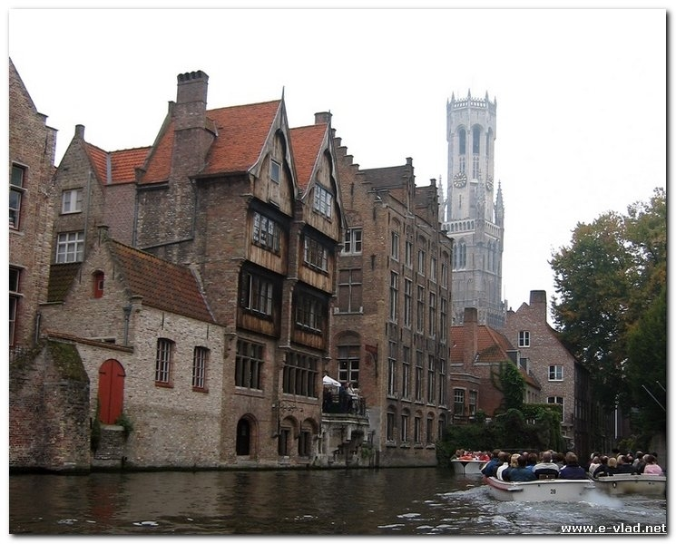 Tourists taking a tour of Bruges by boat. There are many canals in Bruges, Belgium which makes it very easy to move around by boat.