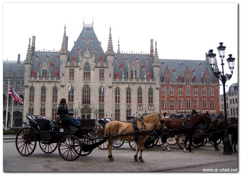Carriage drivers waiting for customers outside the old City Hall building in Bruges, Belgium.