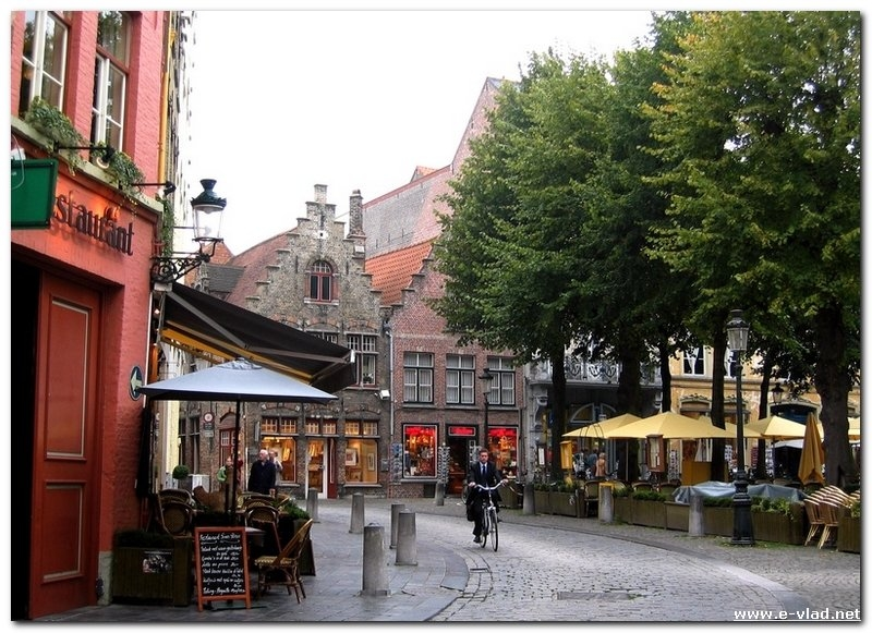 Bruges, Belgium - Man riding a bicycle in front of a local restaurant in Bruges.