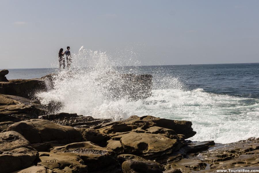 Tourists at the edge of jagged rocks at La Jolla California