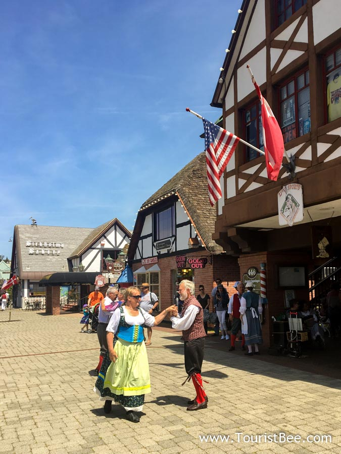 Local people dressed in Danish costumes dancing on the main pedestrian area in Solvang
