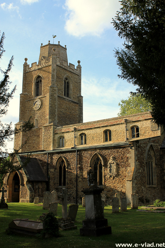 Hemingford Grey, England - St James Church with old tombstones in the courtyard.