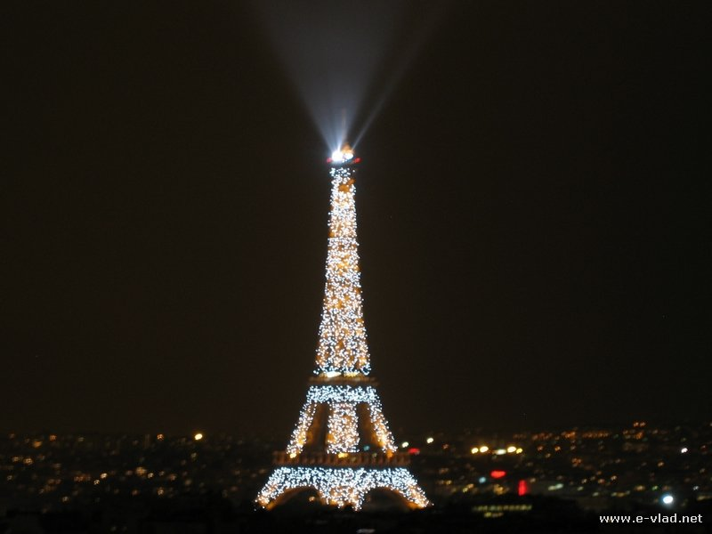 Paris, France - The Eiffel Tower at night seen from the Arch of Triumph in Paris, France.