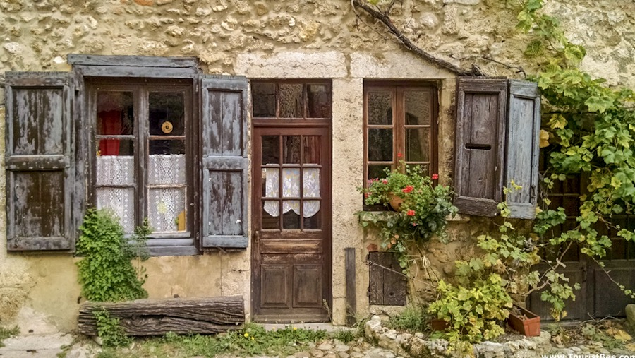 Perouges, France - Beautiful old building with small windows and wooden doors
