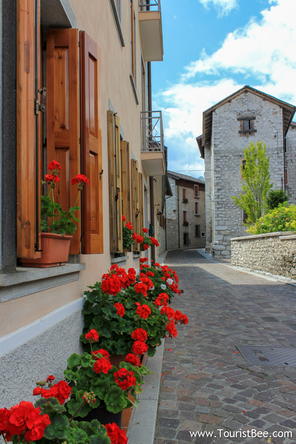 Barcis, Italy - Flowers lining up cobbled street in the village.