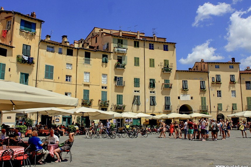 Lucca, Italy - Tourists talking and resting during a hot summer day in the Amphitheater Plaza