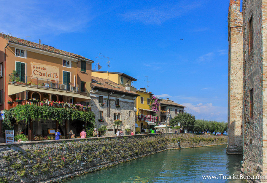 Sirmione, Italy - Water canal and beautiful old buildings and shops right inside the old city walls.