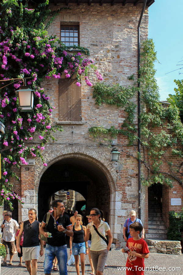 Sirmione, Italy - Tourists walking the old streets and eating gelato.