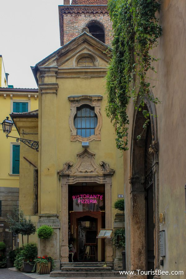 Verona, Italy - The beautiful San Matteo Church restaurant and pizzeria is located behind Porta dei Borsari.