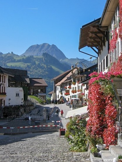 Narrow streets in Gruyeres with the mountains in the background.