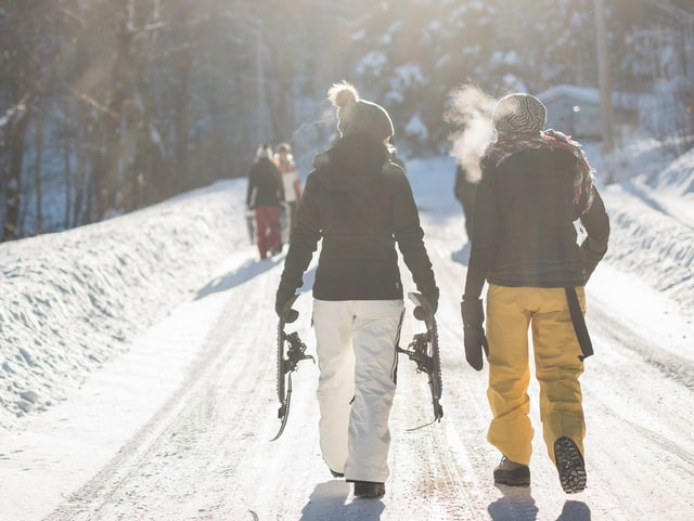 Snowboarders walking up the trail at ski resort